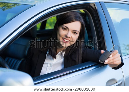 driving concept -happy smiling young woman with car key - stock photo