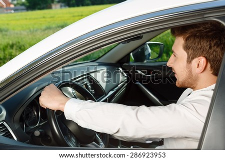Driving forward.  Profile of handsome smiling man with beard driving car in country side.