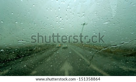Driving in rain with street arrow sign - stock photo