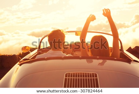 Driving into the Sunset. Happy Young Couple Enjoying the Sunset in Classic Vintage Sports Car - stock photo