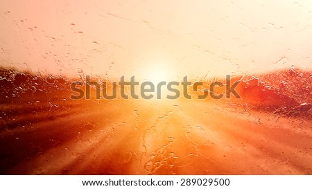Driving on a Highway at Sunset when it starts to Rain. - stock photo