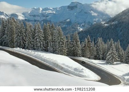 driving on a snowy mountain forest road - stock photo