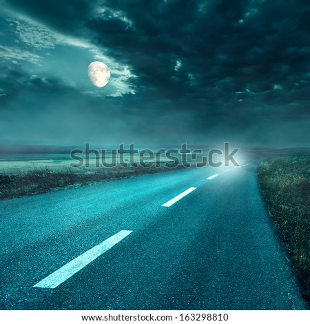 Driving on an empty asphalt road at night - stock photo