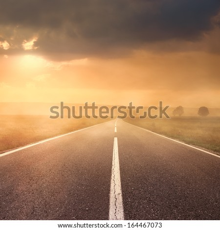 Driving on an empty asphalt road at sunset