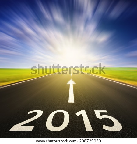Driving on an empty asphalt road in motion blur forward to upcoming 2015 - stock photo