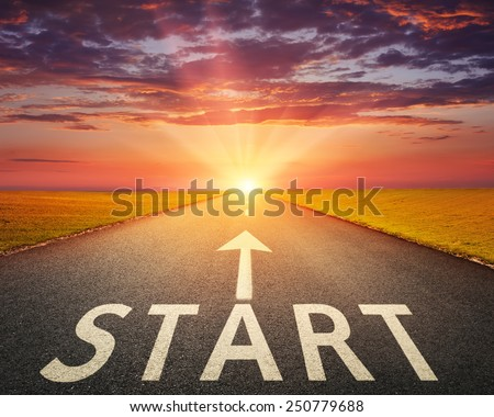 Driving on an empty asphalt road through the agricultural fields at sunset. Concept vision for a new beginning with a sign start and an arrow towards the setting sun. - stock photo