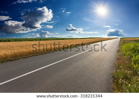 Driving on an empty asphalt road through the agricultural fields towards the setting sun. - stock photo