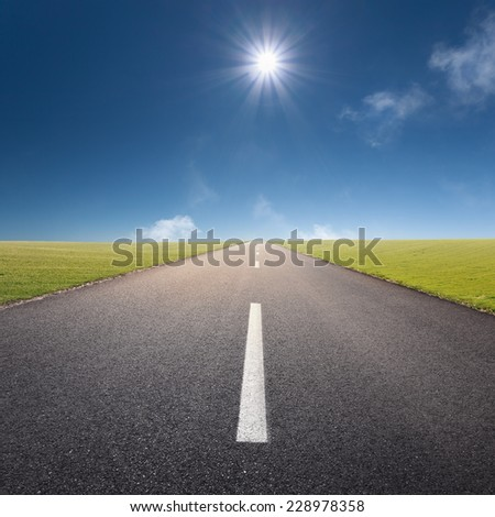 Driving on an empty asphalt road through the idyllic pastures at sunny day - stock photo