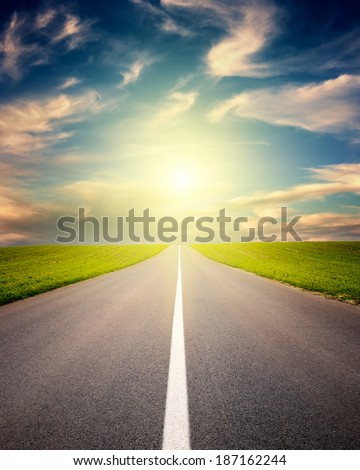 Driving on an empty asphalt road through the idyllic rural landscapes at sunset - stock photo