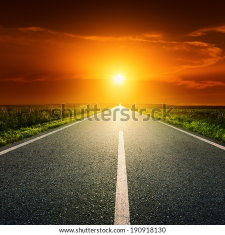 Driving on an empty asphalt road through the idyllic rural scenery at sunset