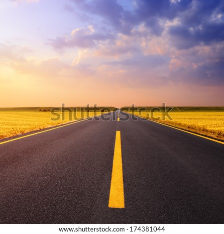 Driving on an empty asphalt road through the wheat fields at sunset - stock photo