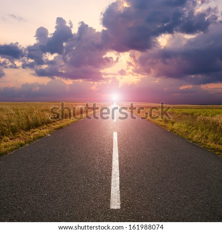 Driving on an empty asphalt road to the rising sun