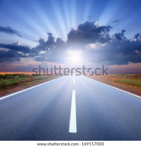 Driving on an empty asphalt road to the sun's rays - stock photo