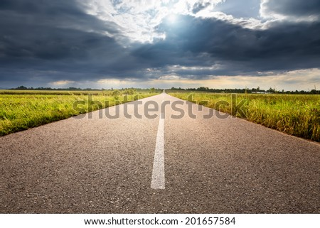 Driving on an empty country road towards the sunlight - stock photo