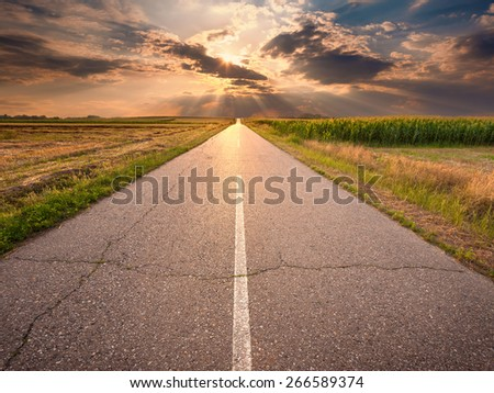 Driving on an empty open road towards the setting sun - stock photo