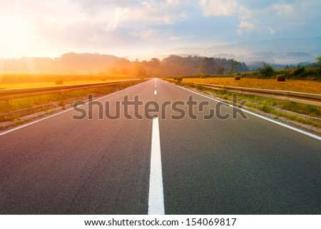 Driving on an empty road to the sun