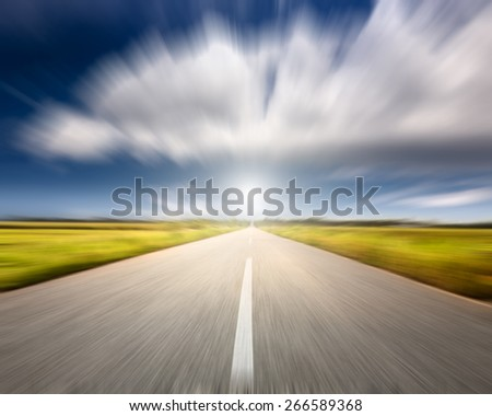 Driving on an empty road towards the big cloud at beautiful sunny day in motion blur - stock photo