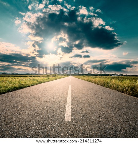 Driving on an empty road towards the setting sun  - stock photo