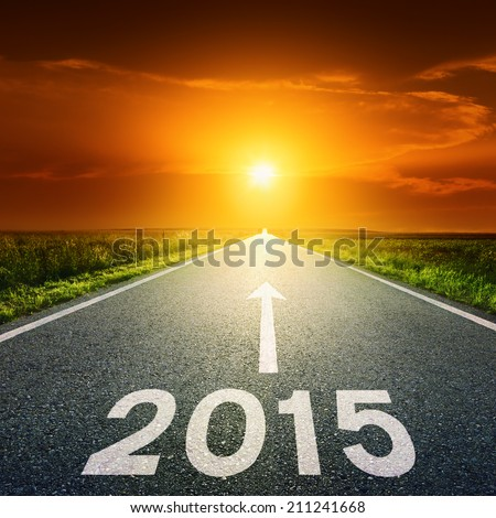 Driving on an empty road towards the setting sun to upcoming 2015 - stock photo
