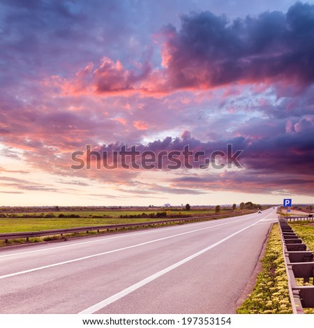 Driving on an open asphalt road at beautiful sunset - stock photo