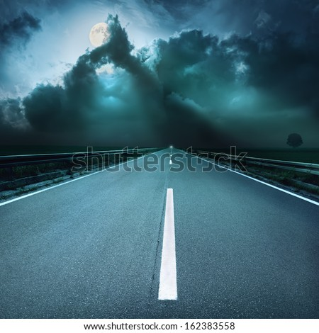 Driving on asphalt road at spooky night - stock photo