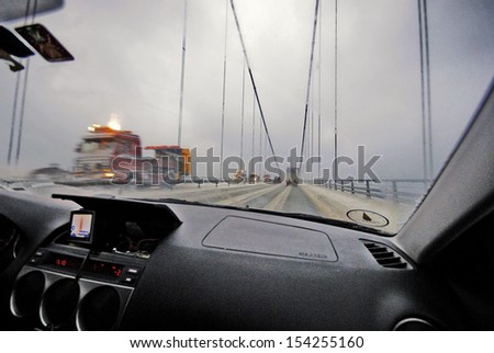 Driving on snowy and cold highway bridge. - stock photo