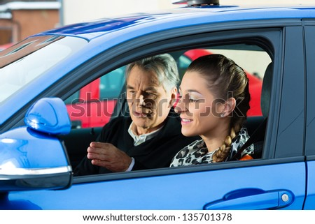 Driving School - Young woman steer a car, maybe she has a driving test perhaps she exercises the parking - stock photo