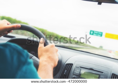 Driving the car on a highway.