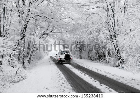 Driving through a snow covered winter wonderland tunnel along country lane - stock photo