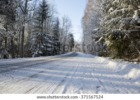 Driving through winter wonderland. An image of a countryside road after first snow in Finland. Image taken during afternoon sun on a cold day. - stock photo