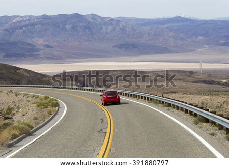 DRIVING TO THE DEATH VALLEY ON HWY 190, March 3, 2016: Small red car is driving to the Death Valley Superbloom