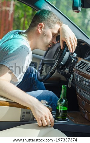 Driving Under the Influence. Man sleeping on the steering wheel. - stock photo