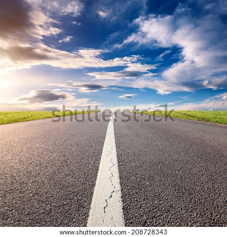 Driving uphill on an empty asphalt road at sunny day