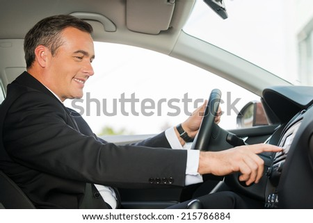 Driving with comfort. Side view of cheerful mature man in formalwear driving car and touching dashboard with finger - stock photo