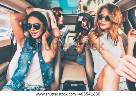 Driving with friends is always fun! Four beautiful young cheerful women looking happy and playful while sitting in car - stock photo