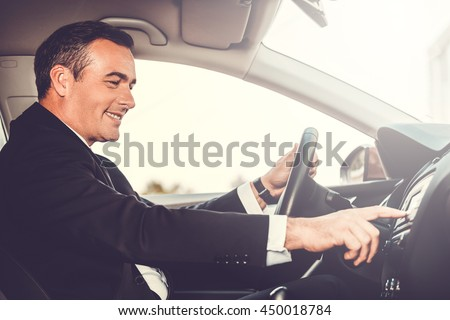 Driving with pleasure. Side view of cheerful mature man in formalwear driving car and touching dashboard with finger - stock photo