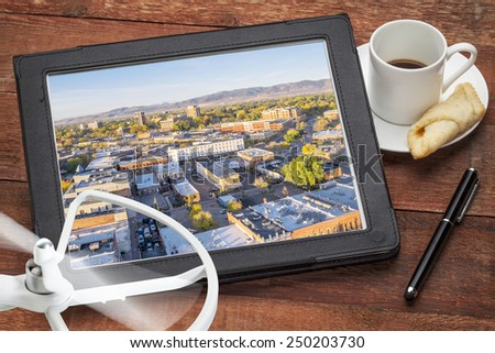 drone aerial photography concept - reviewing aerial pictures of Fort Collins downtown on a digital tablet with a drone rotor and cup of coffee - stock photo