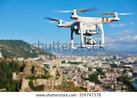 drone quad copter with high resolution digital camera flying hovering in the blue sky over the city
