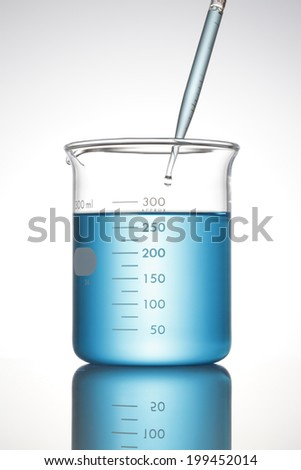 Drop from pipette/ Pipette of Blue Liquid and Beaker - stock photo
