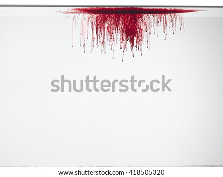 Drop of blood or red color in water, isolated on white background.  - stock photo