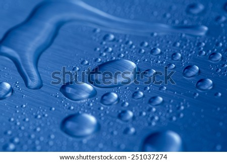 Drop of water on blue background  - stock photo
