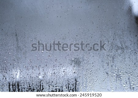 droplets in a window in a snowy day   - stock photo
