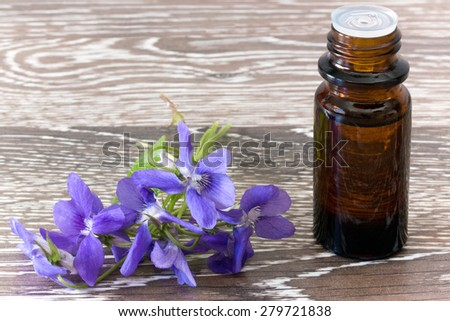 Dropper bottle of bach flower essence on wooden background with blossoms - stock photo