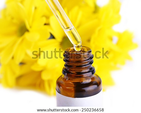 Dropper bottle of perfume with yellow chamomile on white background - stock photo