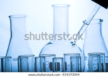 dropping chemical liquid to test tube, science and medical laboratory research concept  - stock photo