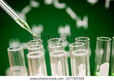 Dropping chemical liquid to test tubes, laboratory research  - stock photo