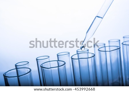 dropping chemical liquid to test tubes, laboratory research and development concept, blue tone  - stock photo