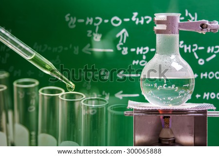 Dropping liquid to test tube with boiling chemical in round bottom flask, laboratory concept  - stock photo