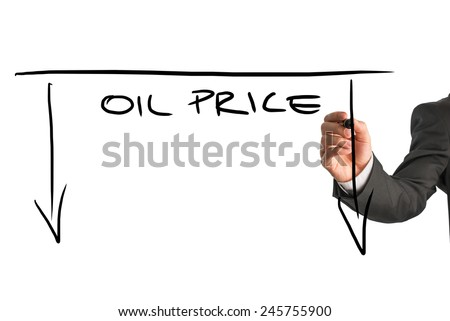 Dropping oil prices concept with a businessman drawing a graph with downward pointing arrows and the words - Oil Price - on a virtual screen or interface over white with copyspace. - stock photo
