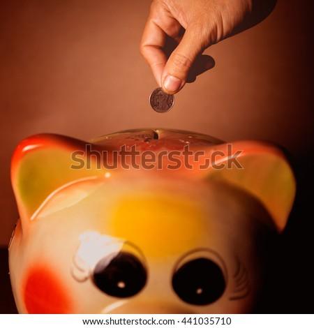 Drops money into piggy bank - stock photo